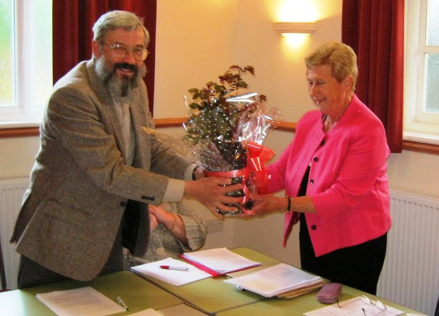 John Powell presents Ann Taylor with a plant in recognition of her service on the Parish Council